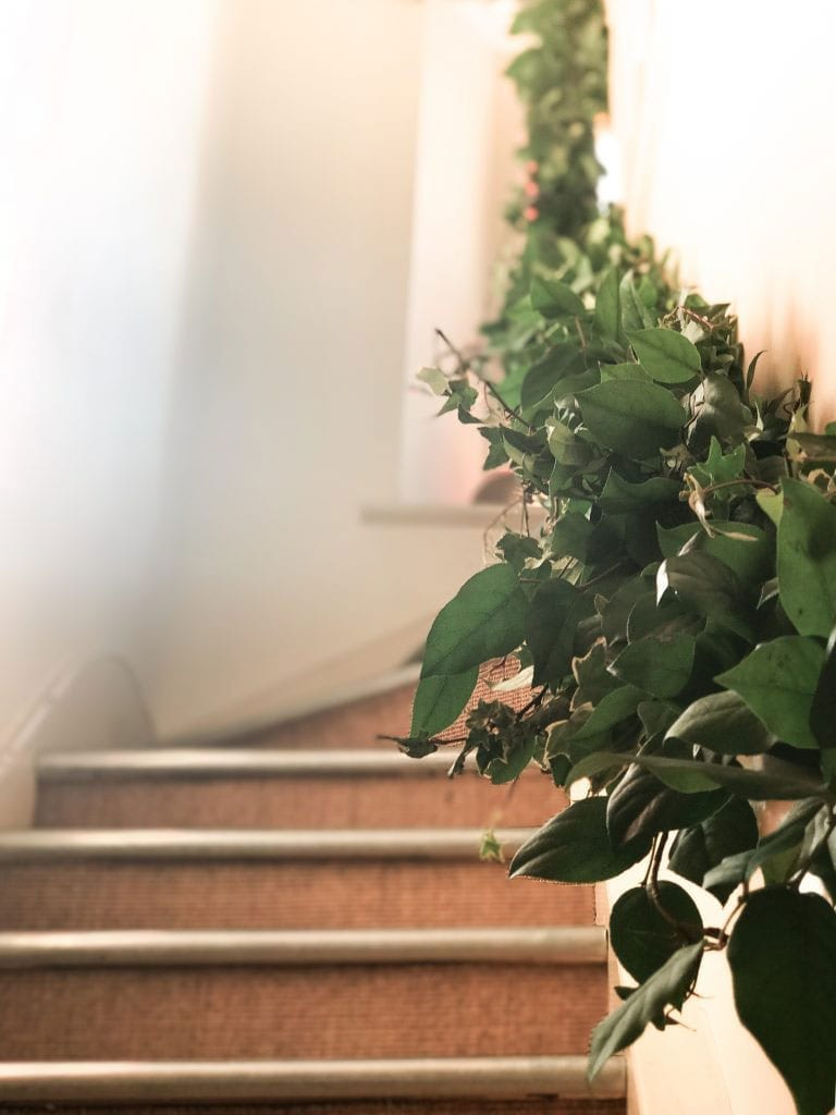 A handmade Foliage Garland Decorating a set of Stairs durring a Wedding at Coombe