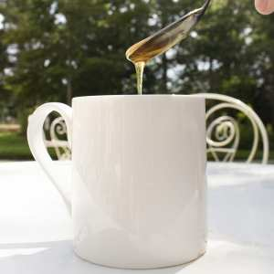 tregothnan branded mug on table with honey being poured into it