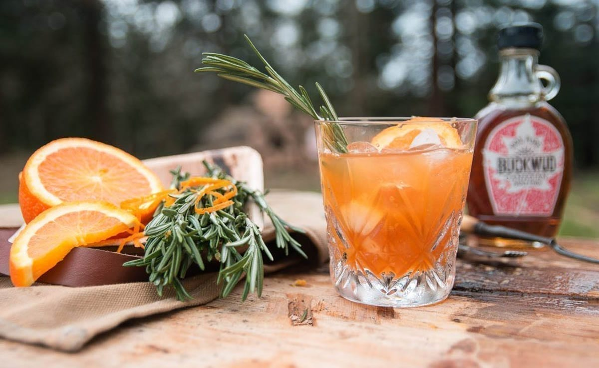 A glass of Smokehouse Iced Tea served with a sprig of Rosemary and a Slice of Orange