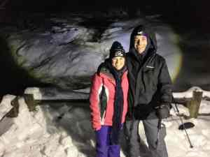 Couple at frozen waterfall at night
