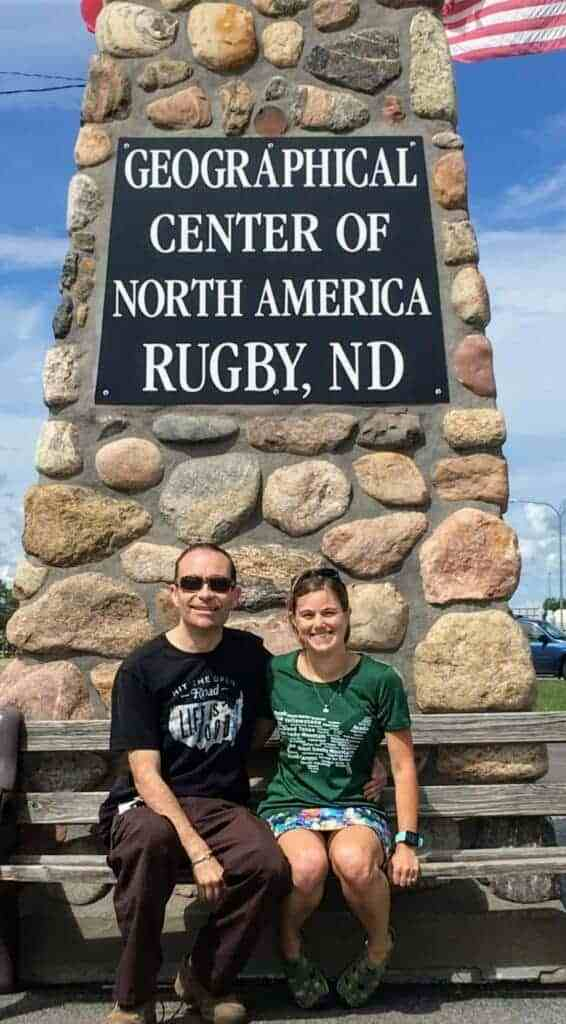 Man and woman seated at Geographical Center of North America pillar