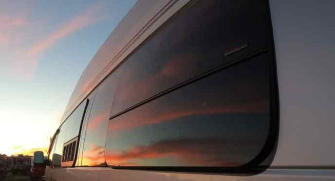 Sunset in side window of van to symbolize dream of nomad life