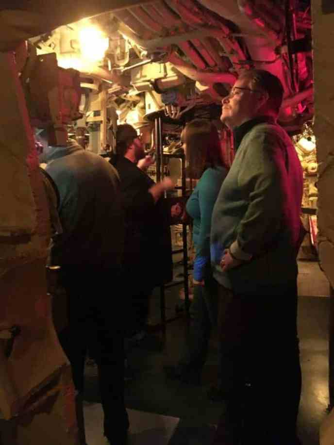 people in WWII submarine control room at modern museum