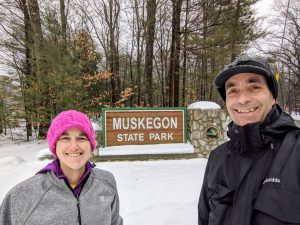 woman and man at entrance sign for Muskegon State Park
