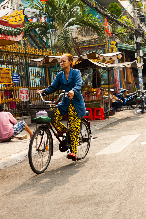 An old lady passes by on her bicycle