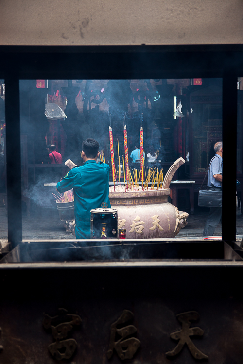 A temple worker clears some of the incense sticks