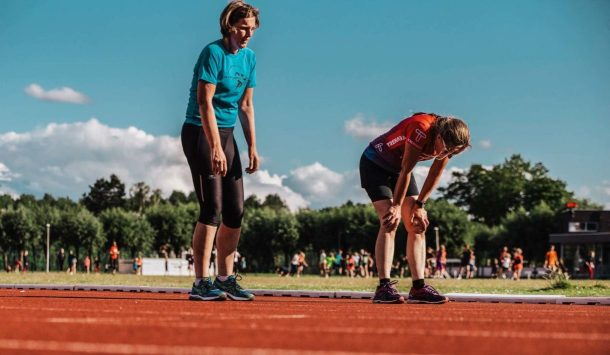 Two women sweating on a running track
