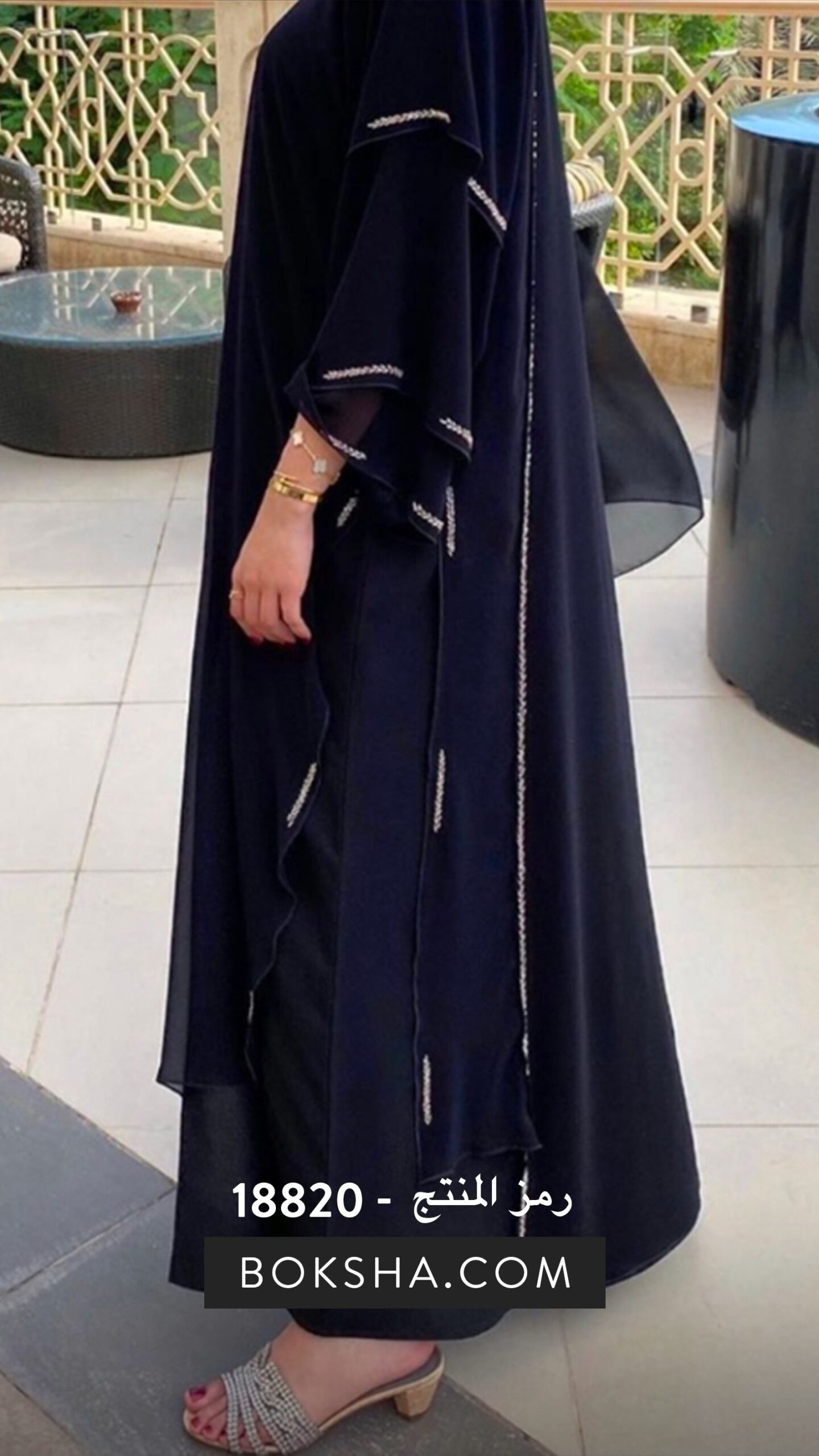 Black abaya featuring a layered chiffon overlay, adorned with embellishments.