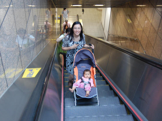 Travelling up a mall escalator with your baby stroller in tow