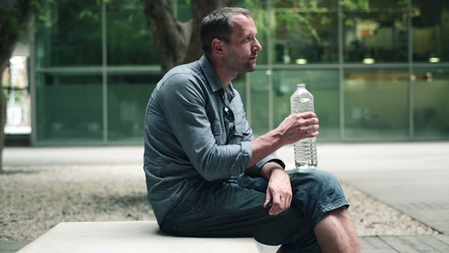 man drinking water on bench