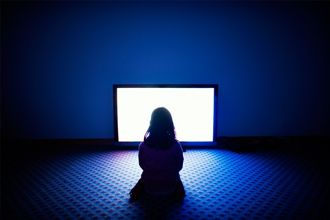 Girl sitting in front of TV