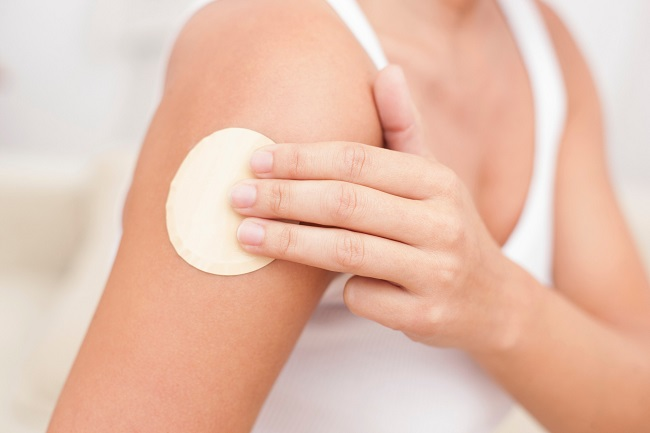 Female getting nicotine patch on arm