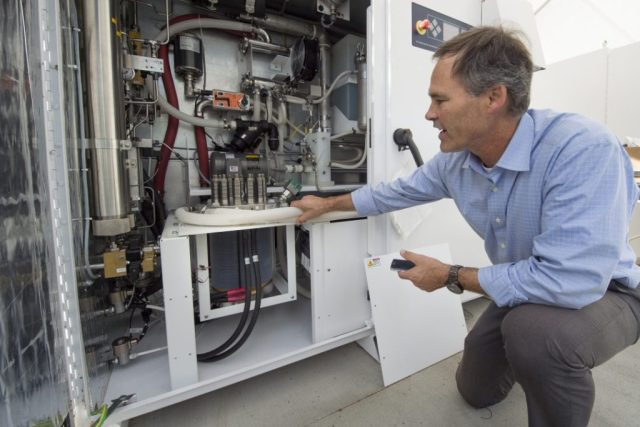 Jack Brouwer, UCI associate professor of mechanical & aerospace engineering and civil & environmental engineering, explains the workings of an electrolyzer, a key component of the power-to-gas system. The device uses renewable electricity to split water into oxygen and hydrogen. The oxygen is released into the atmosphere, and the hydrogen is injected into the natural gas supply line for UCI's power plant. Steve Zylius / UCI