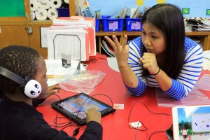 Teacher working on math with a young student who is using an iPad.