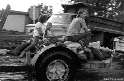 People riding trailer covered with sandbags during flood.