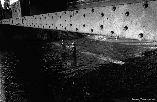 Kids playing in the Provo River under the train bridge.