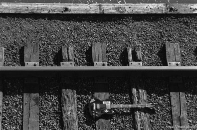 Trent' bass guitar laying on the railroad tracks on the train bridge.