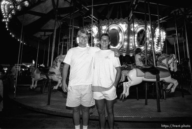 Two guys in front of the carnival merry-go-round.