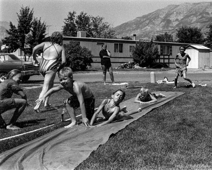 Kids playing slip-and-slide in a trailer park.