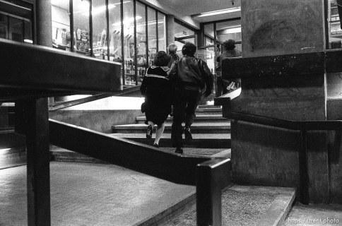 "Couple running through ""mall."""