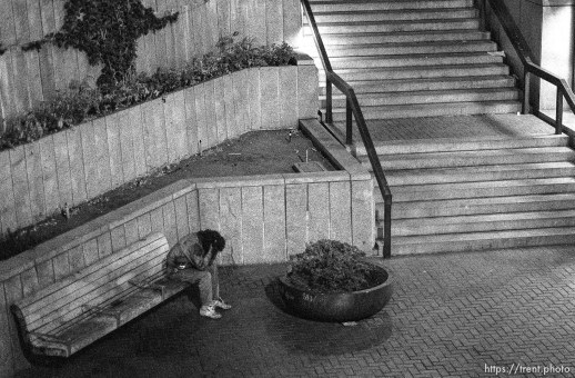 Person with their head in their hands on Market Street at night.