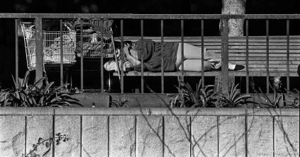 Homeless person sleeps on bench