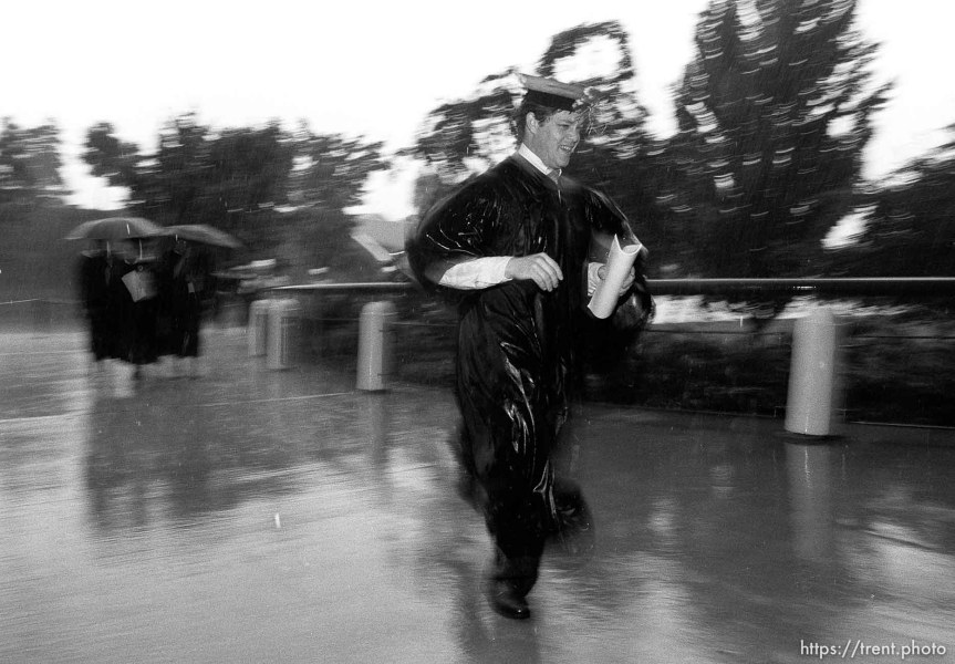 BYU graduates running to their graduation in the pouring rain.