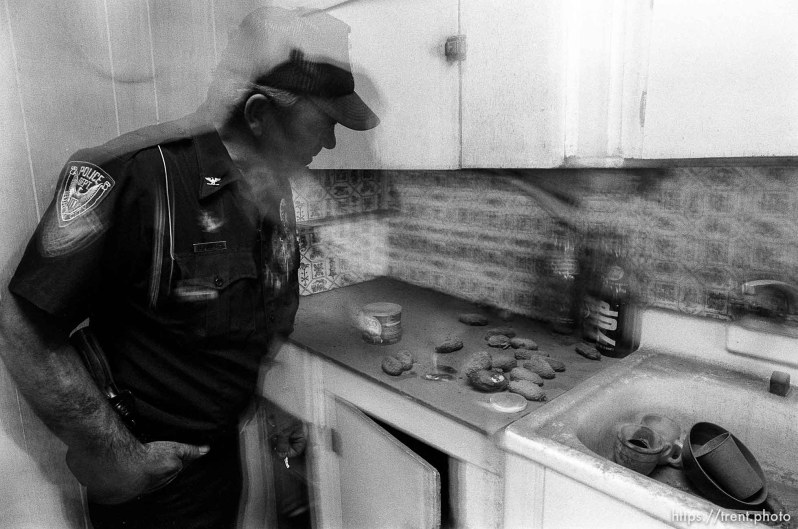 Eureka Police Chief Fullmer examines old potatoes in an abandoned home