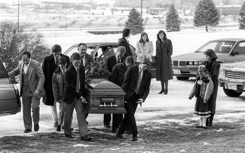 Family carrying casket at funeral of School superintendant (Moss).