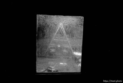 Swingset seen through wet, rainy window in playhouse