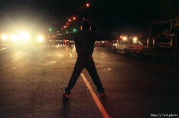 Man stands in middle of street opposing police officers on motorcycles during riots and protests.