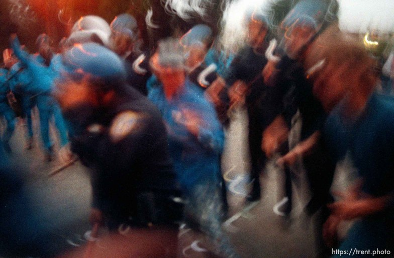 Police charge in (slow shutter) during riots and protests.