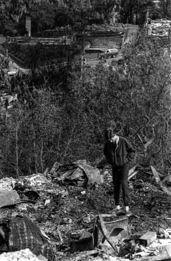 Man standing in the remains of his family's home after the Oakland Hills Fire.