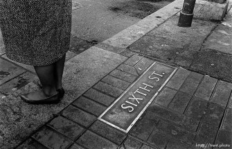 "Woman's feet and ""Sixth St"" plaque on ground."