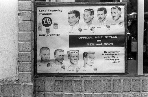 """Official Hair Styles for Men and Boys"" sign in barbershop window."