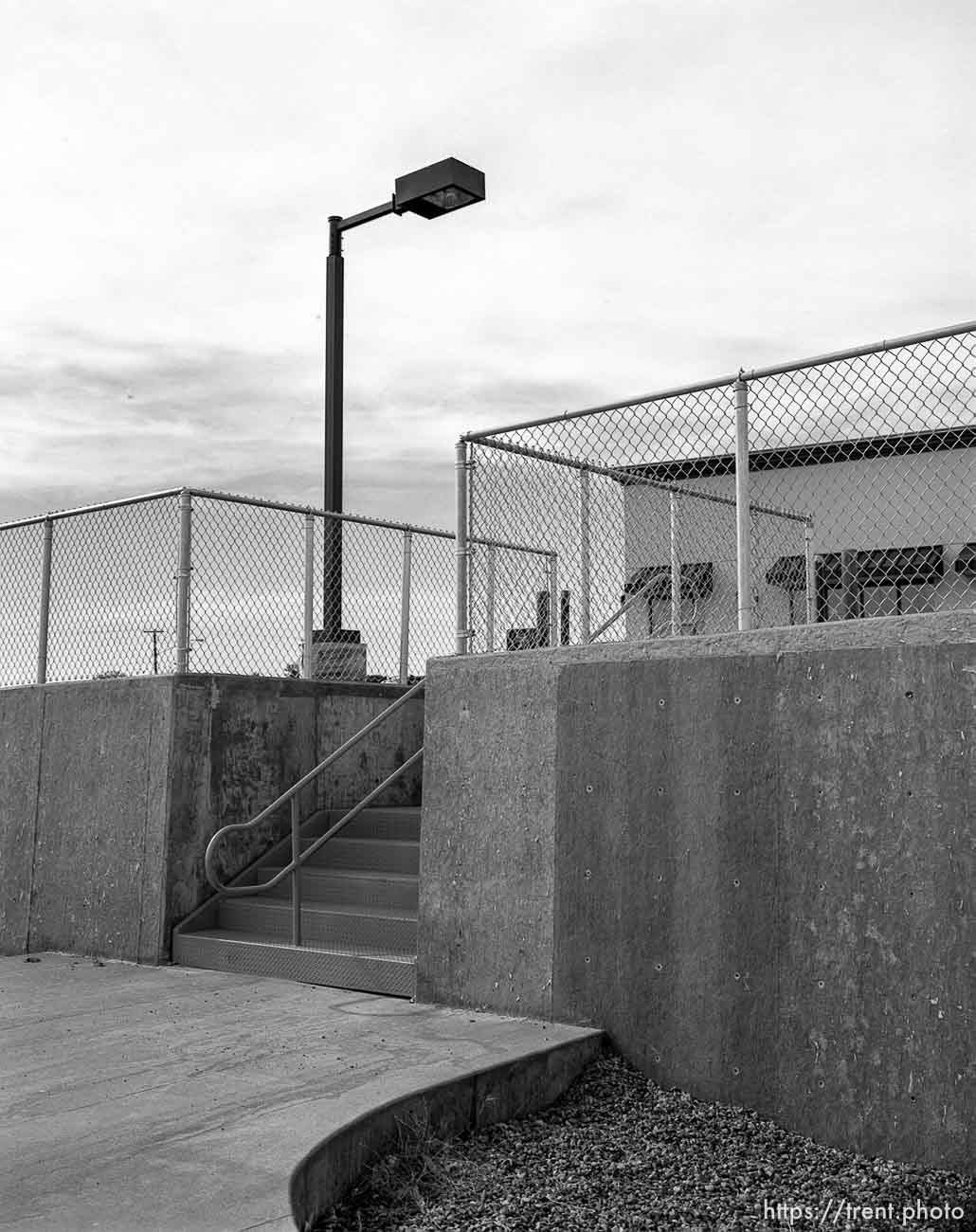 Stairs, chain-link fence, streetlamp in motel parking lot.