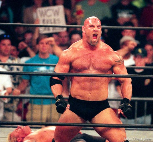 Goldberg celebrates in front of a prone Curt Hennig at WCW's Bash at the Beach.