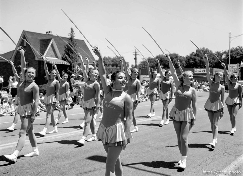 Cyprus High School Spinnakers drill team march with sabres at the 4th of July parade on Main Street.