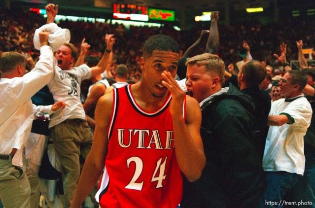 Utah's Andre Miller walks past Utah State fans celebrating their win over 9th ranked Utah at Utah vs. Utah State.