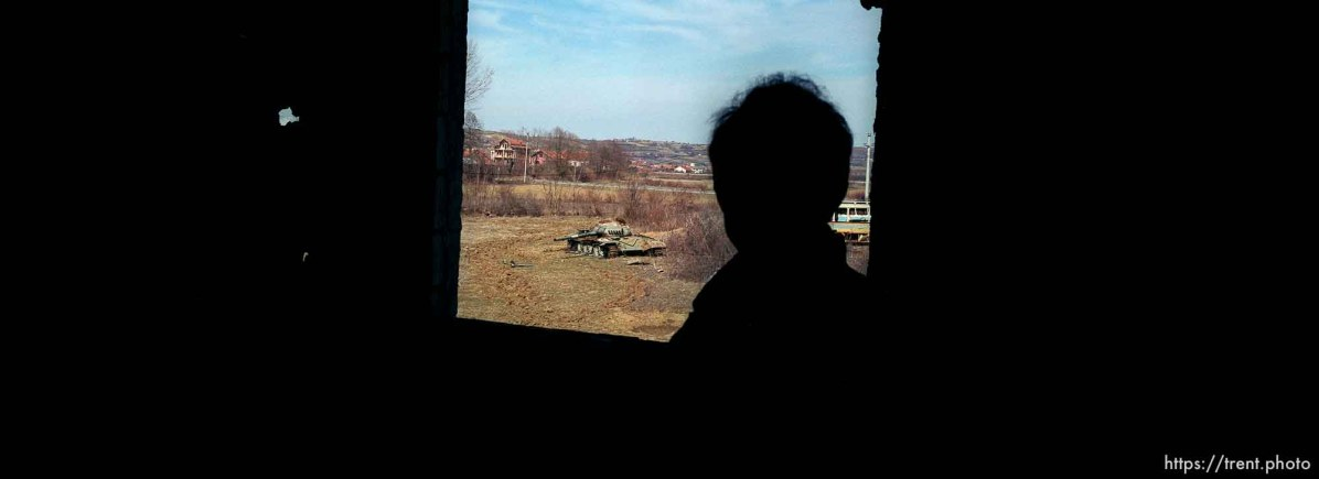 Naim Begiri looking out of a window of his uncle's home, where he hid from Serbs during the war. Outside is a destroyed Yugoslav tank.