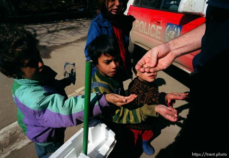 UNMIK police officer Zane Smith hands coins to Roma children outside the UNMIK police station.