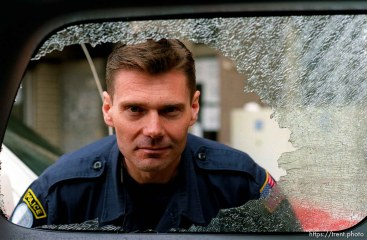 UNMIK police officer Zane Smith looking through the broken glass window on a police vehicle.