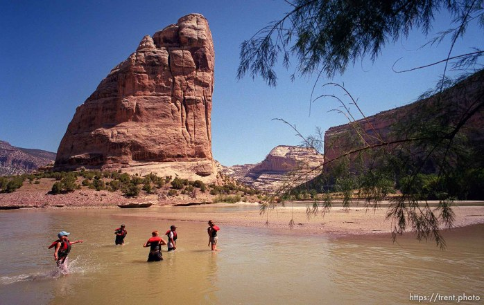 Kids play in the water at Echo Park, with Steamboat Rock in the background on a Native American river trip through Lodore Canyon and Dinosaur National Monument.