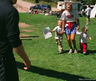 Laura Vaughan races across the finish line with her children, Wildon (4) and Emma (2) at the end of the race, Sundance Ski Resort. Wasatch 100 Endurance Run.