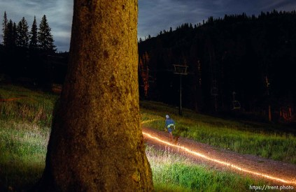 A runner's flashlight marks the trial in the moonlight in the time exposure near Brighton. Wasatch 100 Endurance Run.