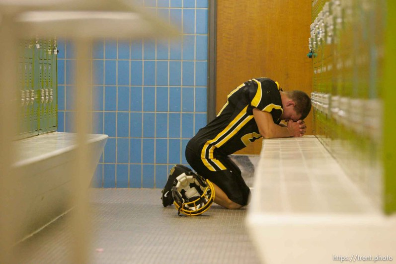 Cottonwood's Cody Williams prays pre-game in the locker room. Cottonwood vs. Highland high school football.