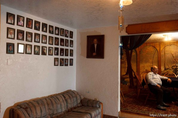 Marvin Wyler in his home with portraits of his 34 children