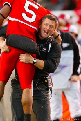 Utah coach kyle whittingham lifts up Utah wide receiver Brent Casteel (5) after casteel scored in the final two minutes. . BYU wins with no time on the clock. Salt Lake City - Utah vs. BYU college football at Rice-Eccles Stadium.