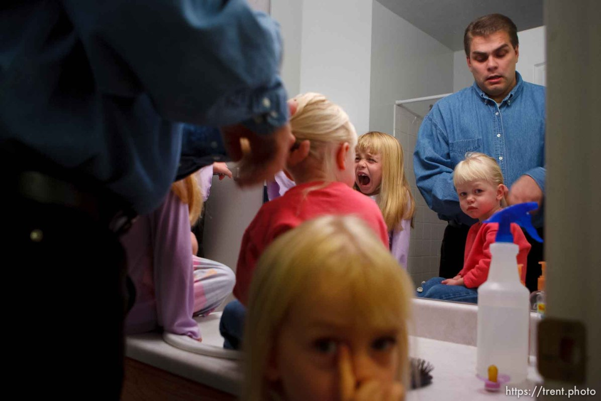 Tooele - Joseph Lappi brushes the hair of his daughters (left to right: Daria, Sophie, and Lillian (bottom)) at 5:40am, getting them ready for the day.. Lappi came back from serving in Iraq to find his wife pregnant with another man's child and himself the sole caretaker for his four children. Oldest to youngest: Joseph Lappi Jr, Daria Lappi , Lillian Lappi , and Sophie Lappi .