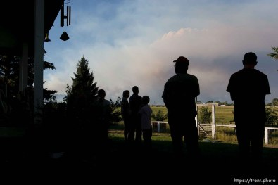 Neola - Members of the Houston family watch from the front lawn of the family home as smoke rises from an out-of-control wildfire in the Ashley National Forest near Roosevelt had burned 14,000 acres in the Unitah Basin by Saturday morning and claimed the lives of three people, including George and Tracy Houston. ; 6.30.2007